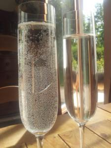 Po lewej stronie szklanka z wodą, na której osadziły się bąbelki, po prawej szklanka z wodą bez bąbelek